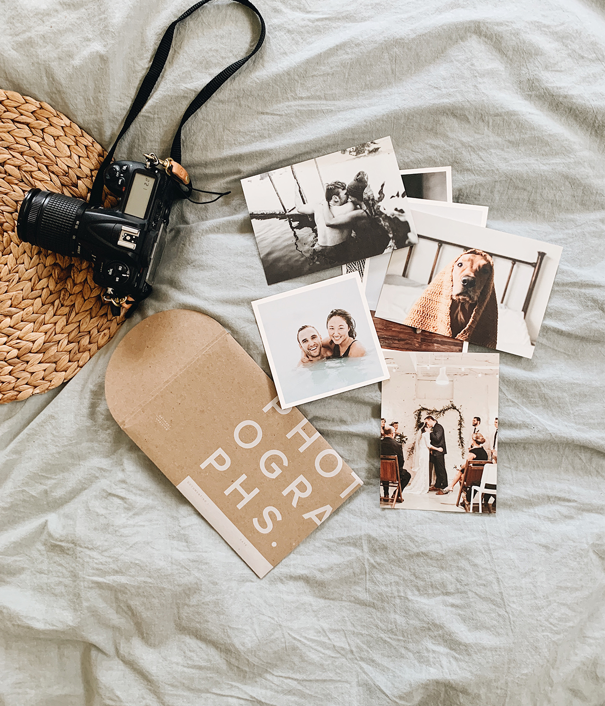 Photo prints on bed next to camera and hat
