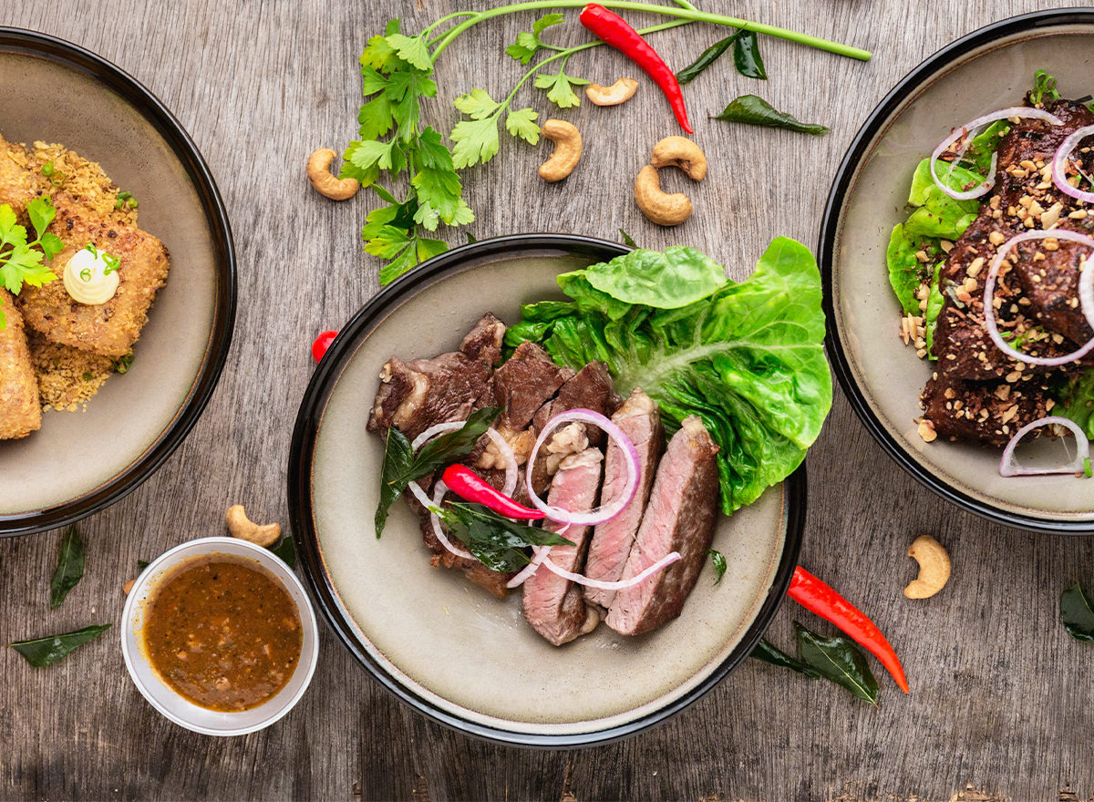 Three delicious looking dishes with a steak bowl in the middle