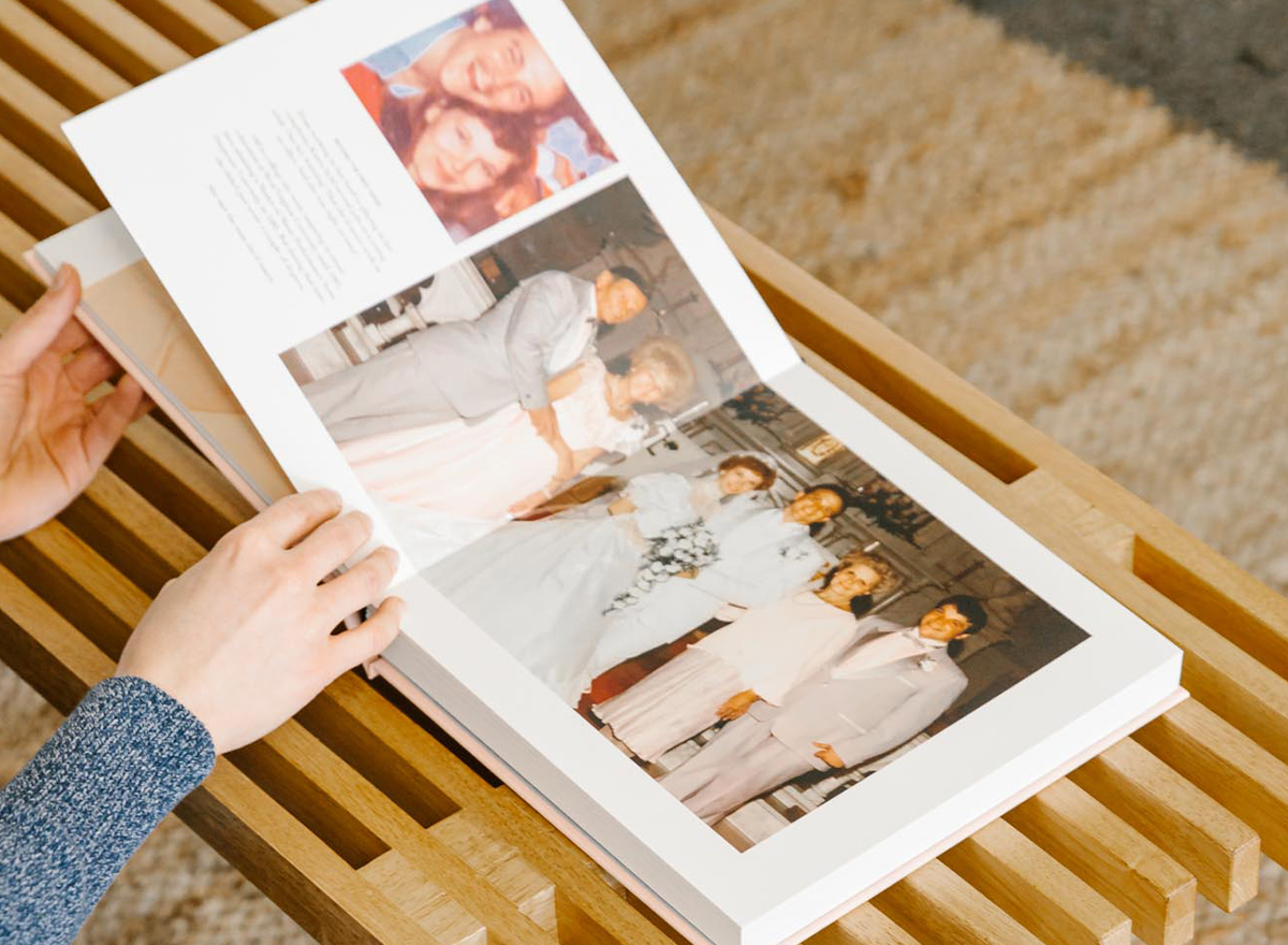 Hands flipping through family history book printed in Artifact Uprising Layflat Photo Album
