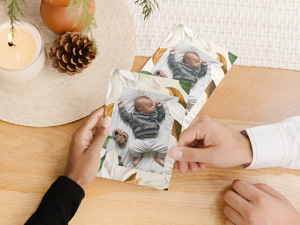 Hands holding Artifact Uprising Holiday Cards featuring baby photo