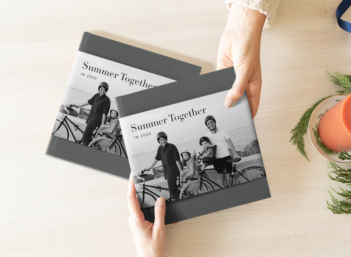 Hands exchanging photo album with duplicate photo album on table below