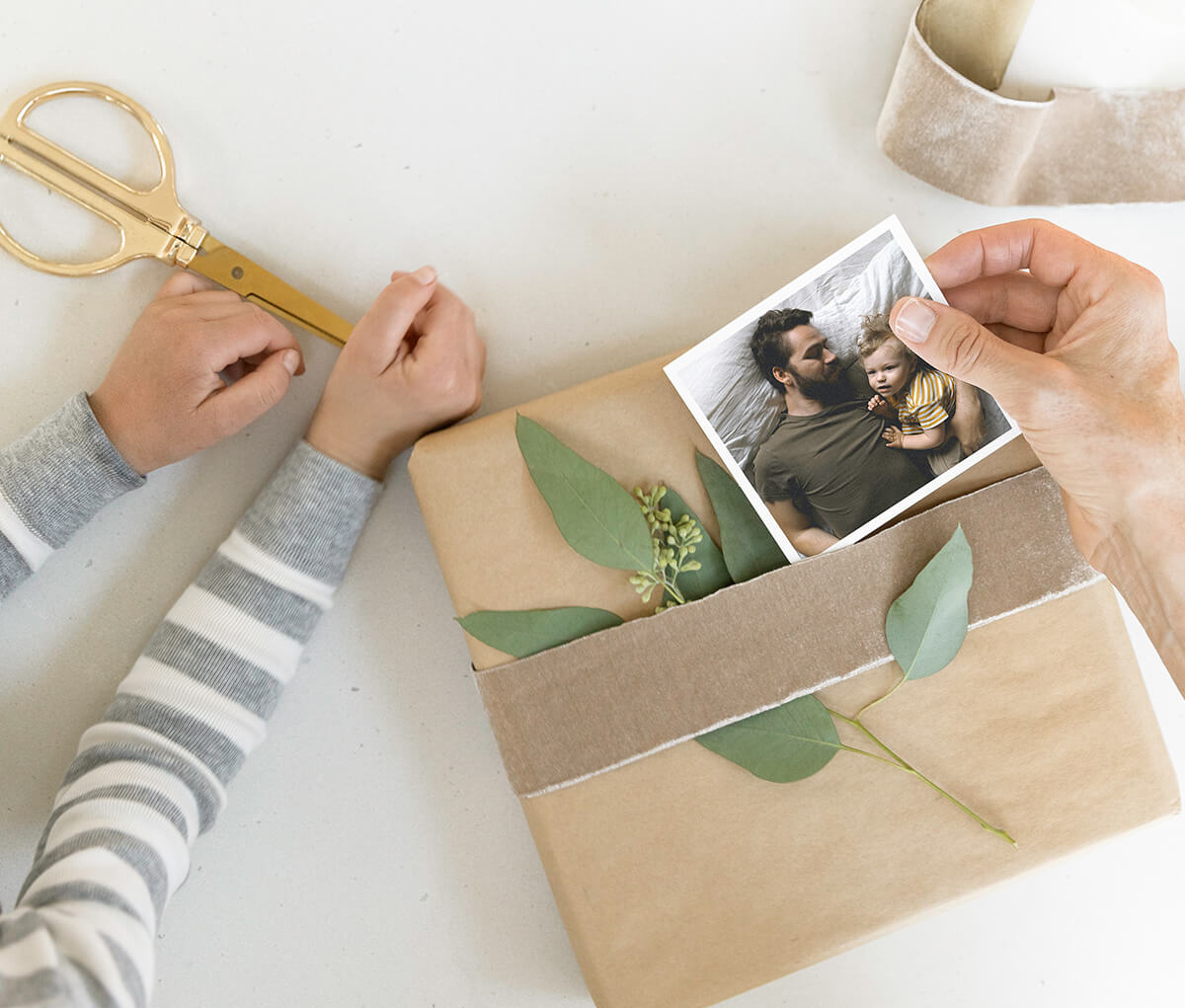 hands slipping photo print under ribbon of wrapped gift