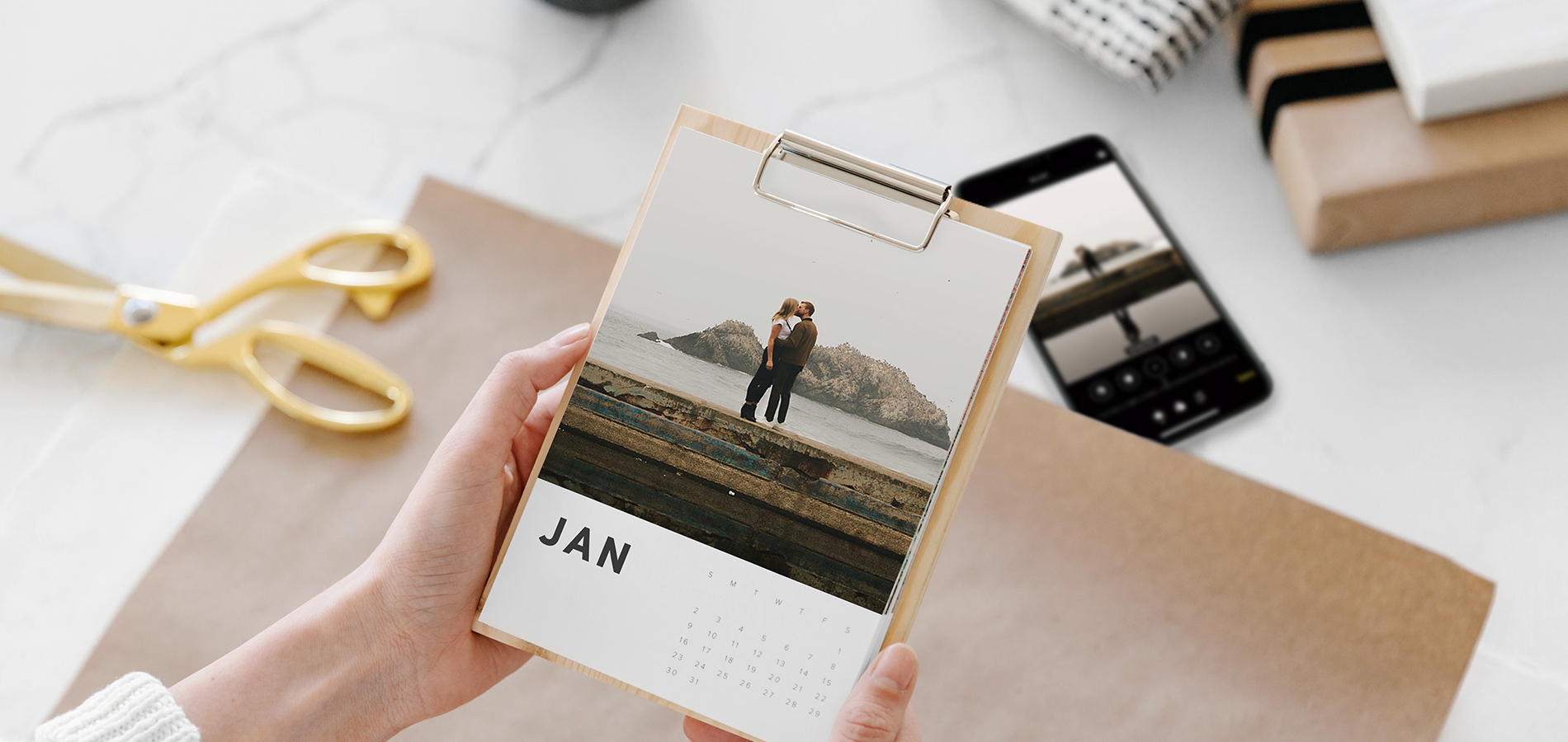 Hands holding photo calendar that is about to be gift wrapped