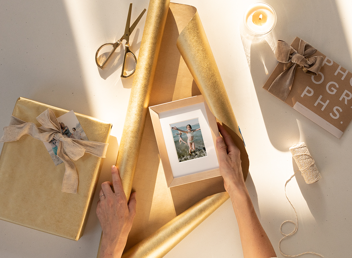 hands wrapping wooden tabletop photo frame in gold wrapping paper