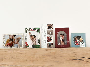 Five Artifact Uprising holiday photo cards lined side by side on a wooden mantel