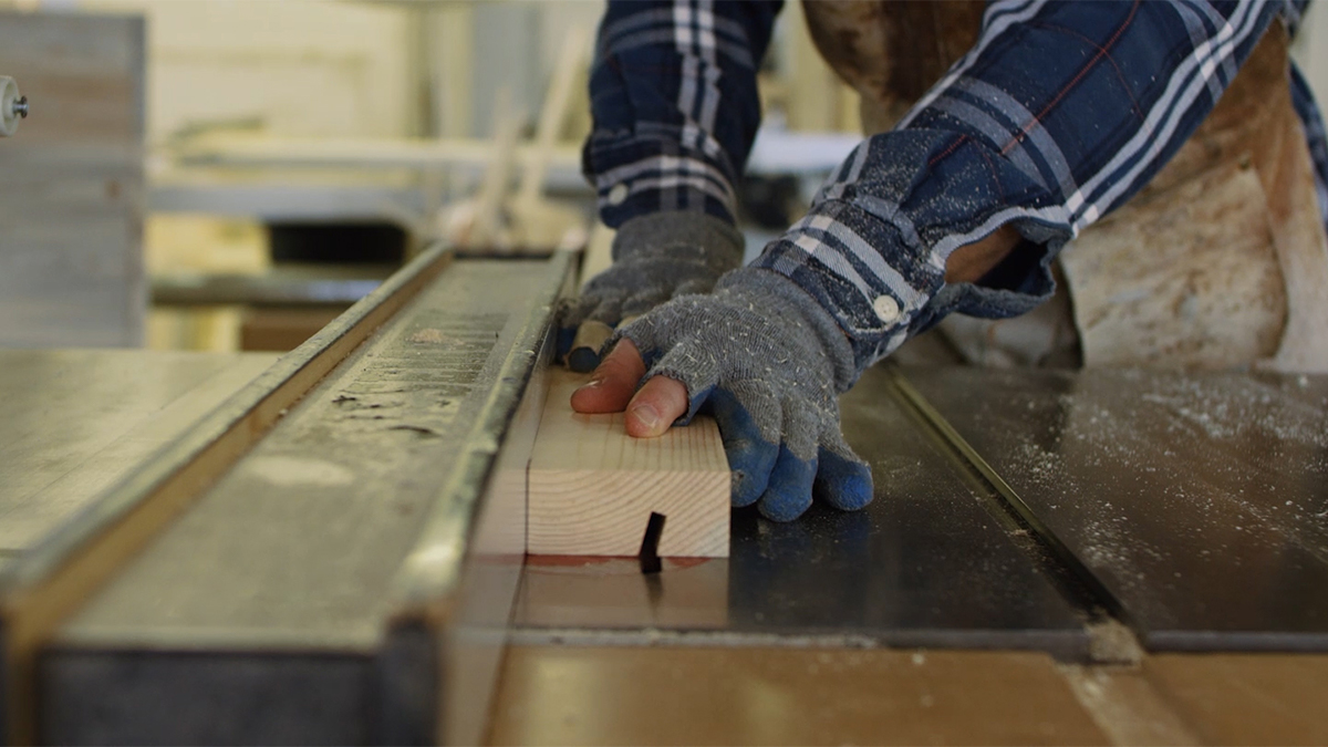 Hands cutting reclaimed wood on table saw