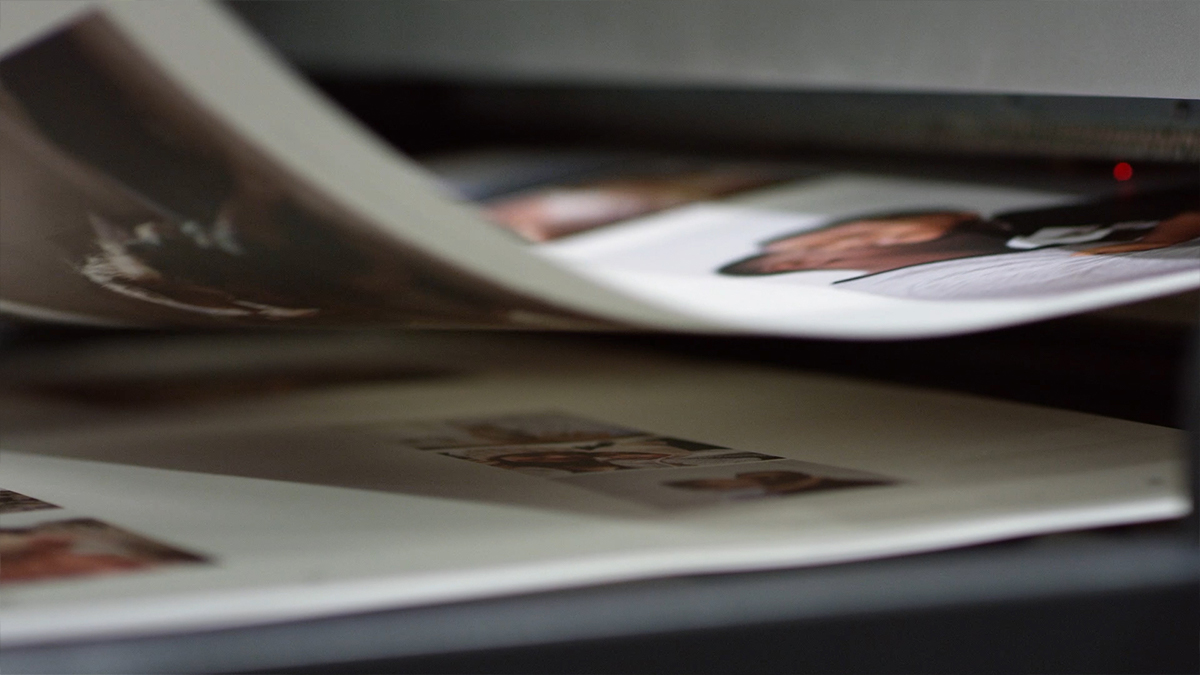 Pages of a photo book rolling off of the printer