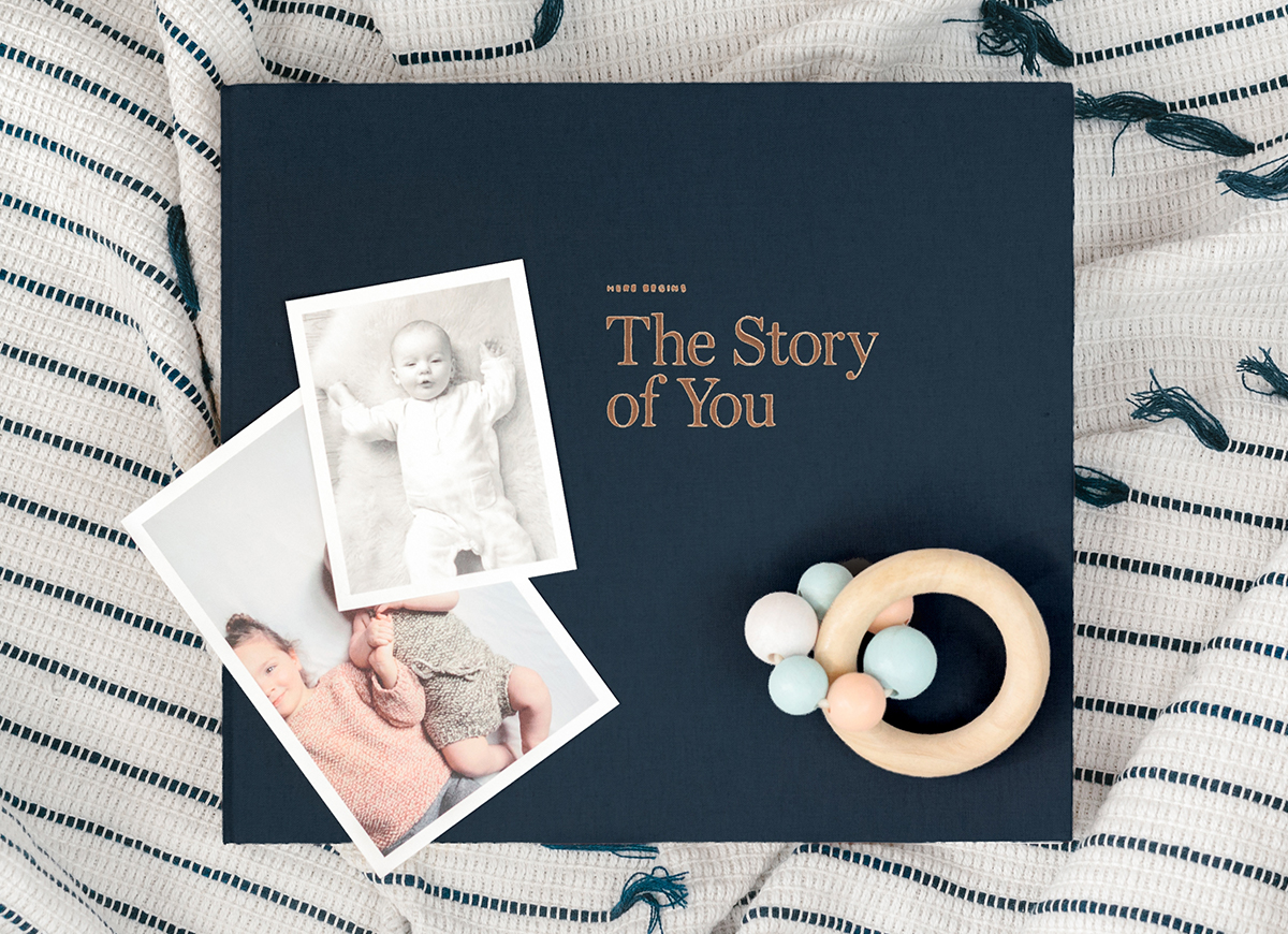 Midnight Blue Story of You Baby Book with rattle and baby photos resting on cover