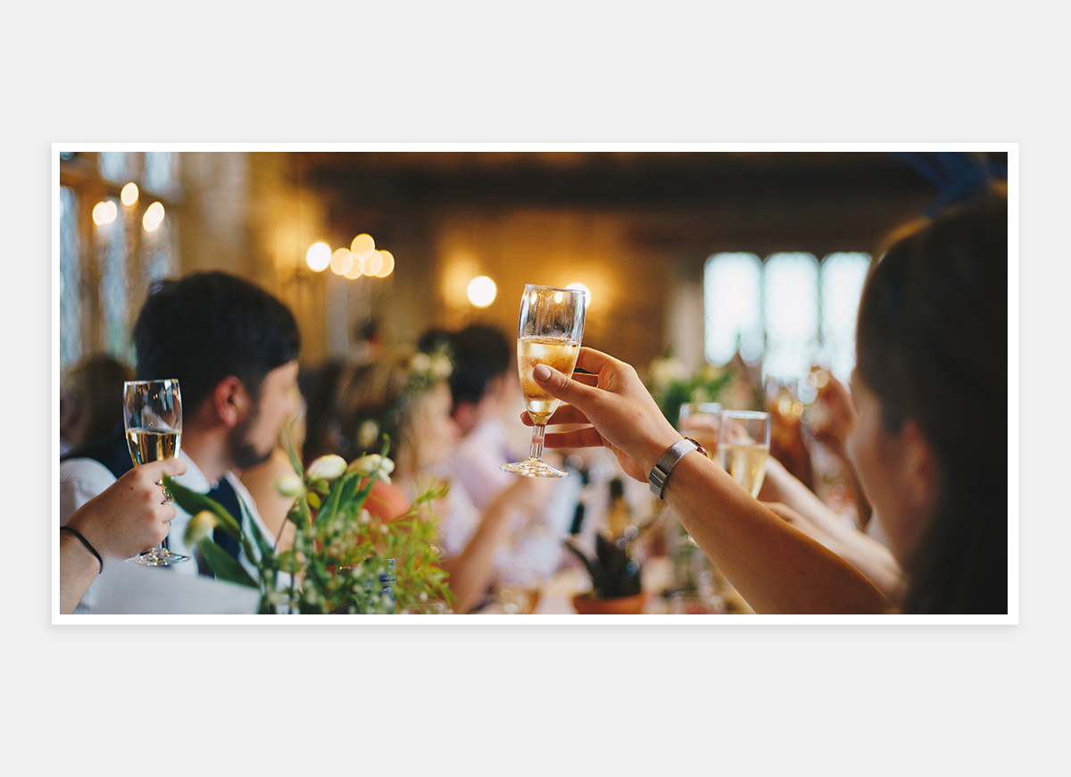 Two-page photo in wedding album of hands toasting champagne