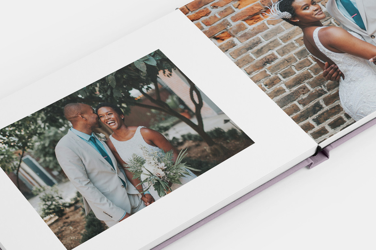 Image in photo book of bride and groom posing in front of textured brick wall