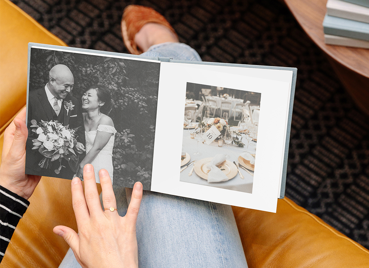 Woman's hands flipping through Everyday Photo Book filled with wedding photos