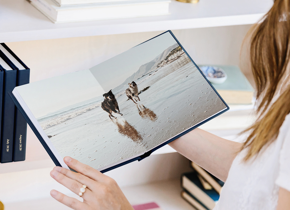 Woman holding Everyday Photo Book with panoramic spread of two dogs running along the beach