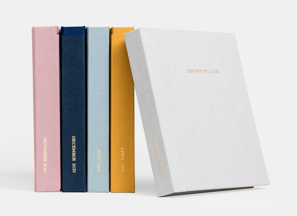 Four Everyday Photo Books in different colors lined up showing spines with fifth book flipped to show cover