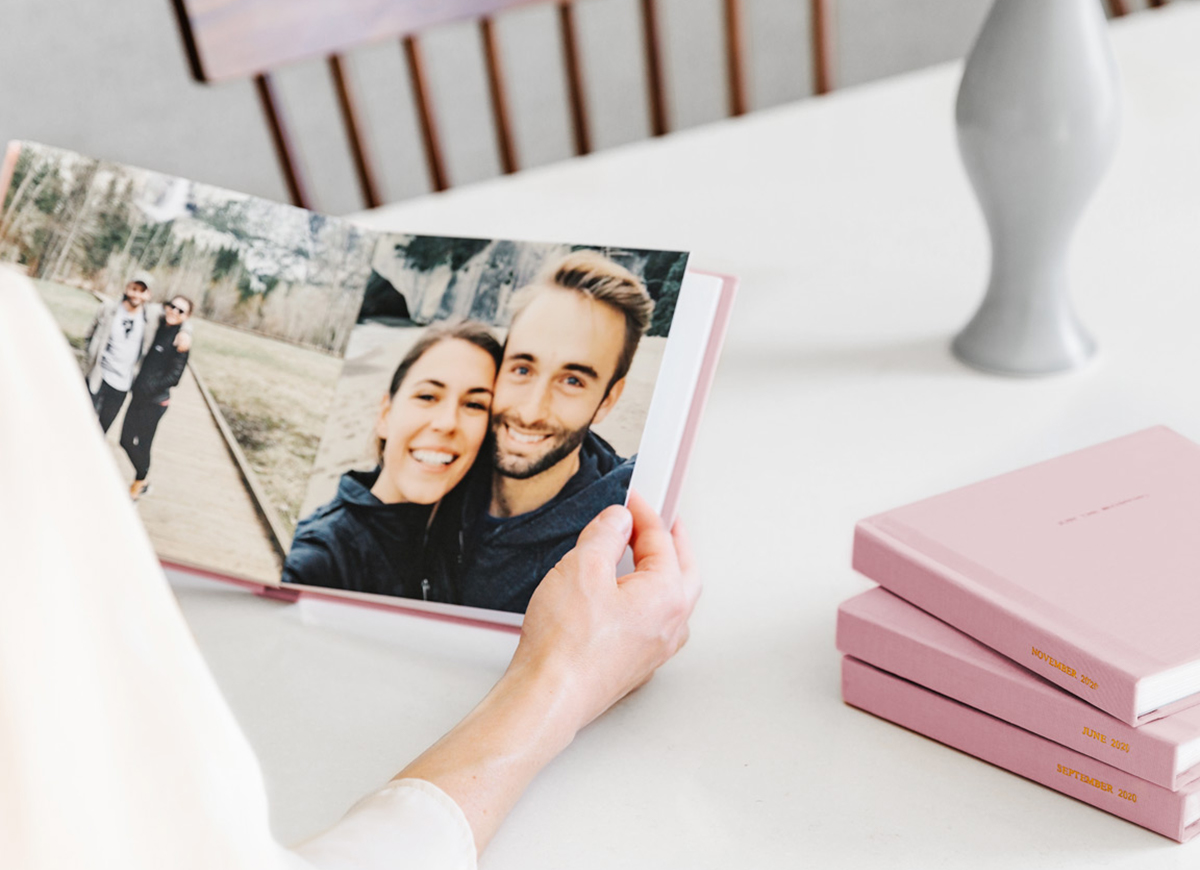 Woman holding an open, pink Everyday Photo Book filled with couple photos