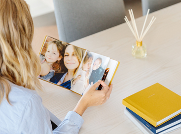 Woman at table flipping through Everyday Photo Book filled with kids' photos