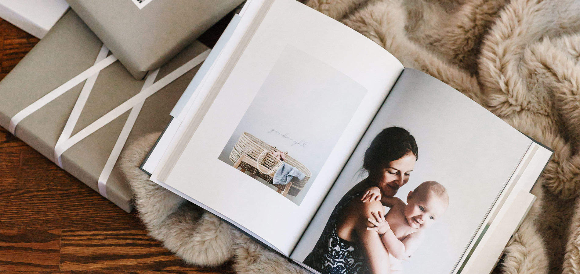 gift boxes next to photo book featuring full page image of mother and baby