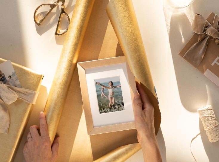 Hands wrapping framed photo in gold wrapping paper