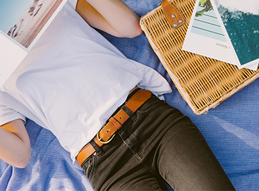 Woman lying on blanket reading softcover photo book by artifact uprising
