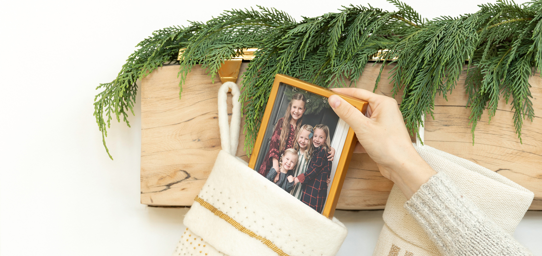 Hand placing small framed photo inside of stocking