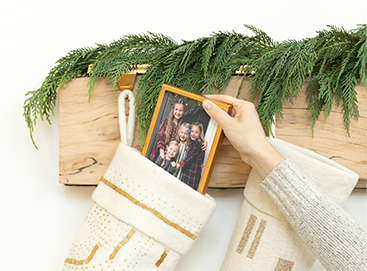 Hand slipping small framed photo into stocking hanging from mantel