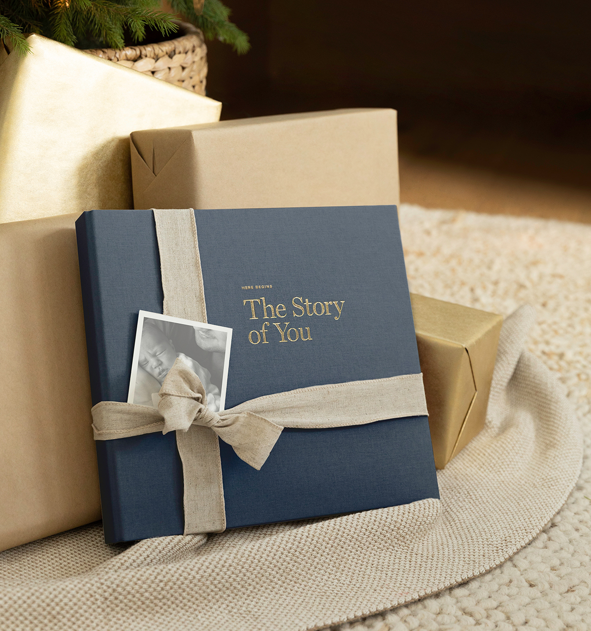 Artifact Uprising Story of You Baby Book wrapped with ribbon next to wrapped gifts