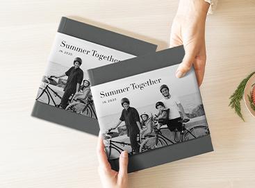 Hands exchanging photo album with duplicate photo album on table beneath