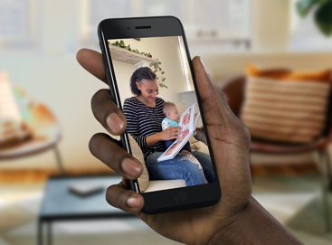 Hand holding phone for FaceTime with woman and child opening gift