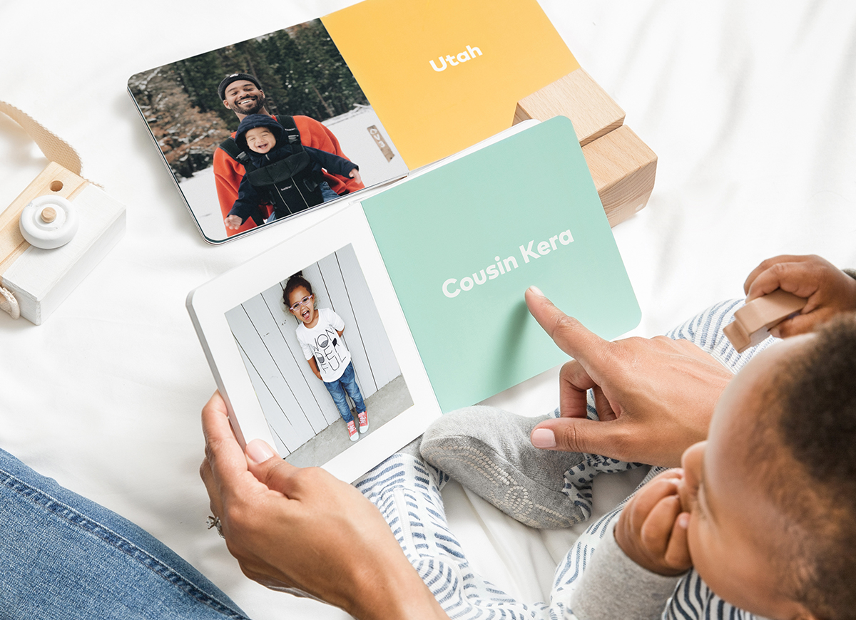 Mother and baby reading baby book filled with family members' photos and names
