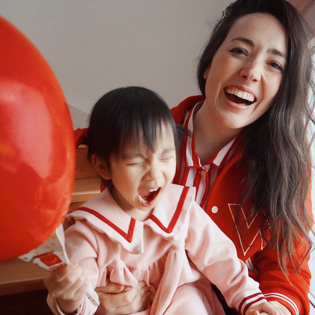 Photo of mother holding daughter who is holding a red baloon