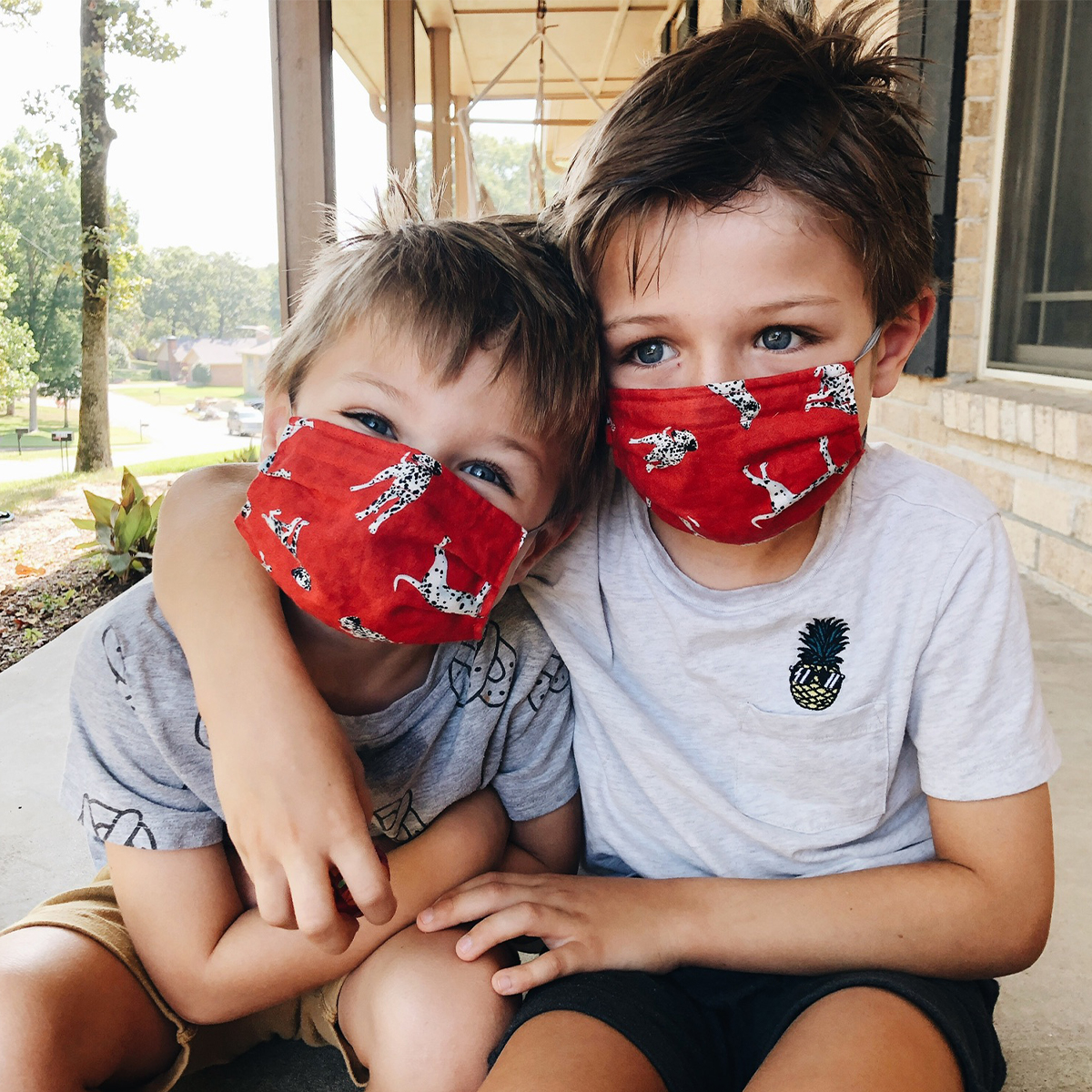 Two little boys smiling and wearing masks