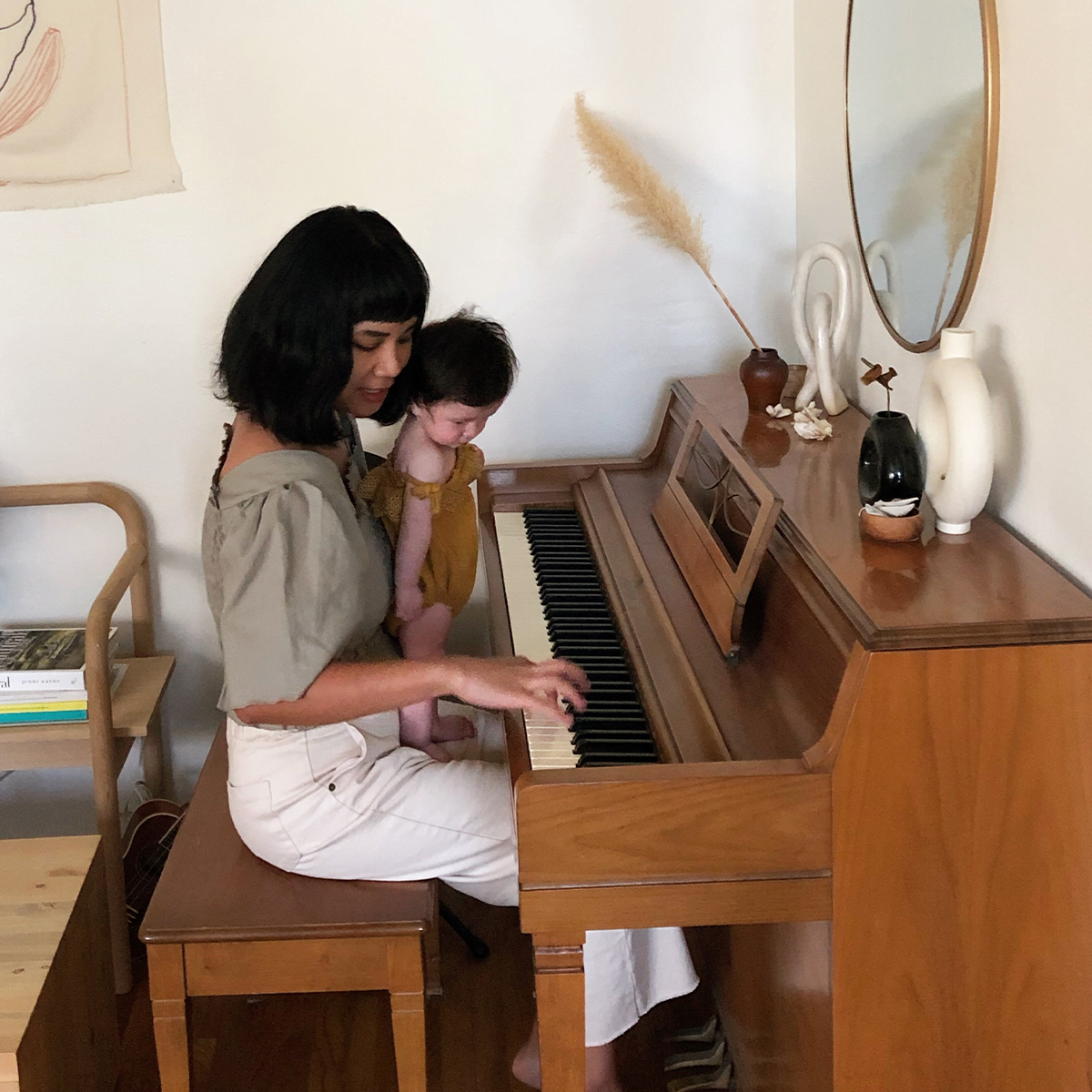 Mother and infant sitting in front of piano