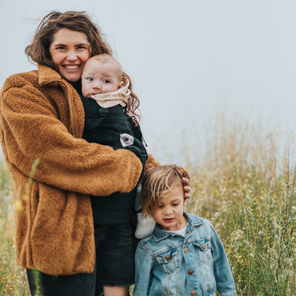 Mother, baby, and toddler standing in scenic field