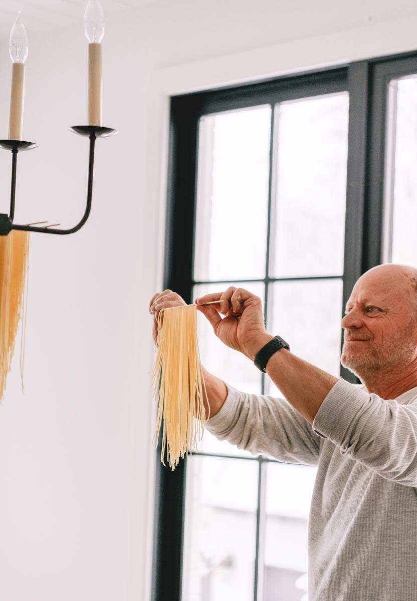 Man hanging homemade pasta
