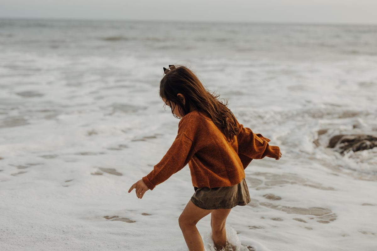 Little girl playing in the afternoon tide