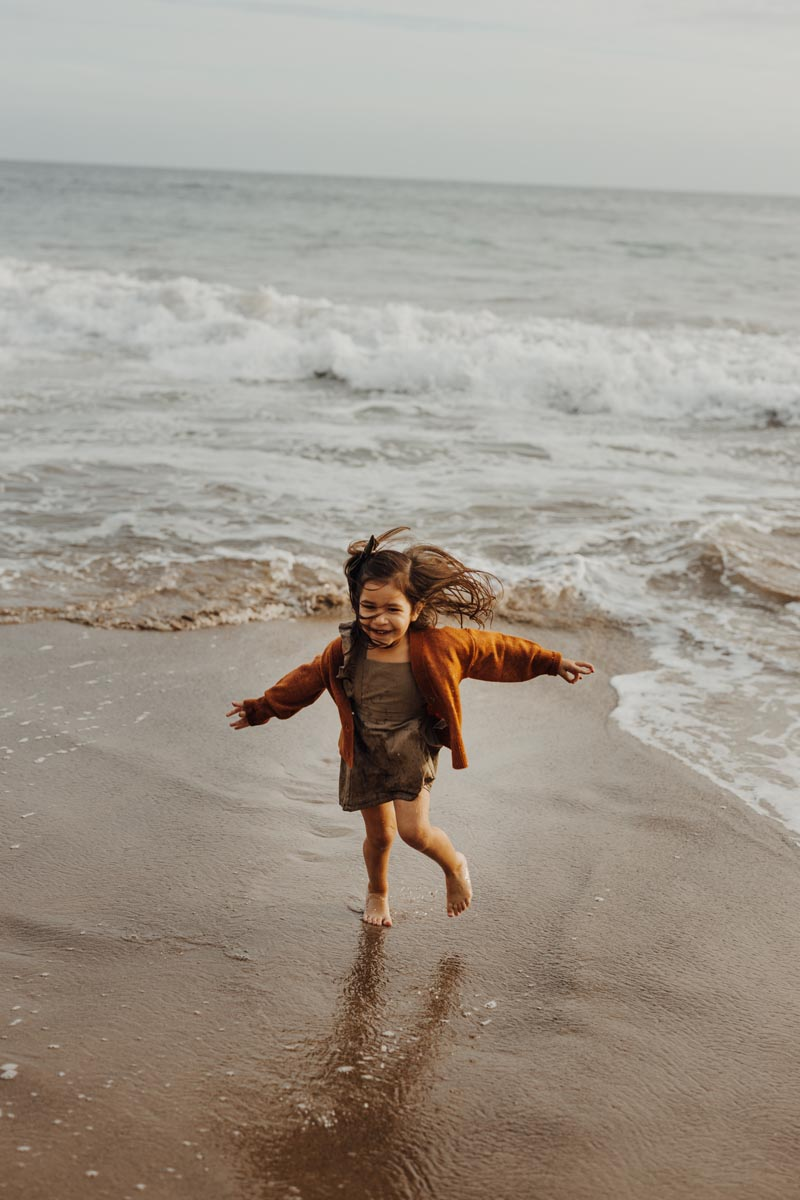 Little girl laughing as she runs from tide rolling in