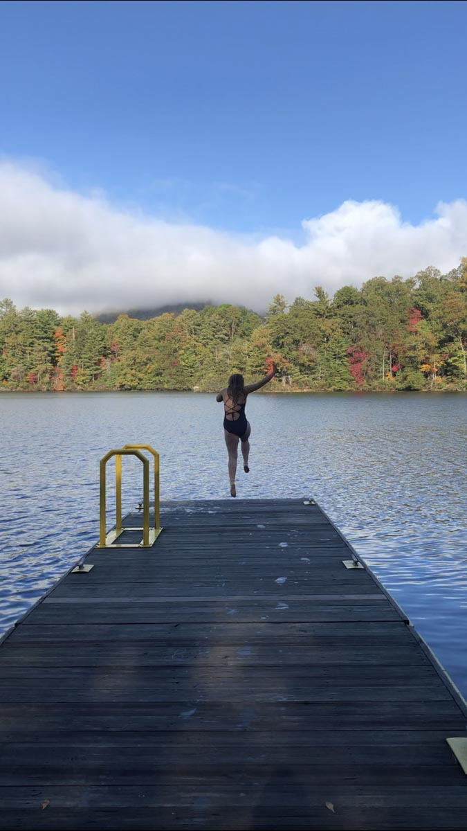 Photo of girl jumping off the edge of a dock into a lake