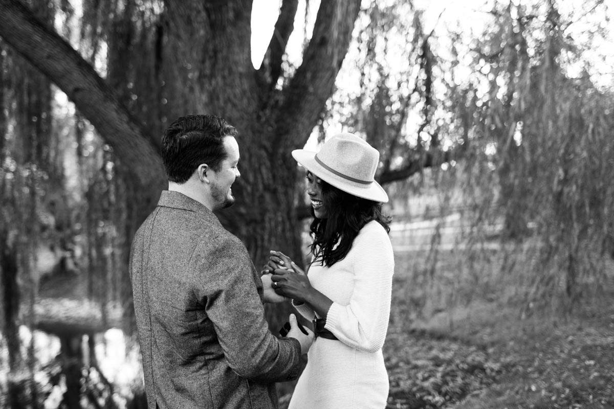 Photo of couple laughing in front of weeping willow