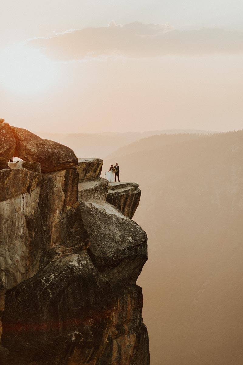 Photo of bride and groom at the edge of a cliff in Yosemite