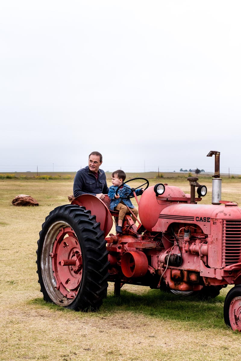 Toddler riding tractor with grandfather