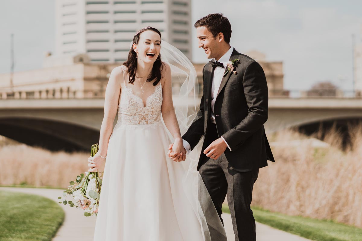 Photo of bride and groom holding hands and laughing