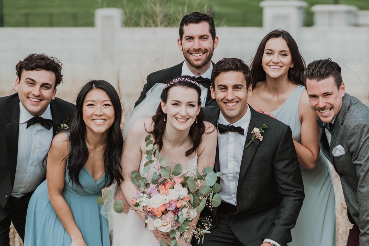 Photo of wedding party with bride and groom