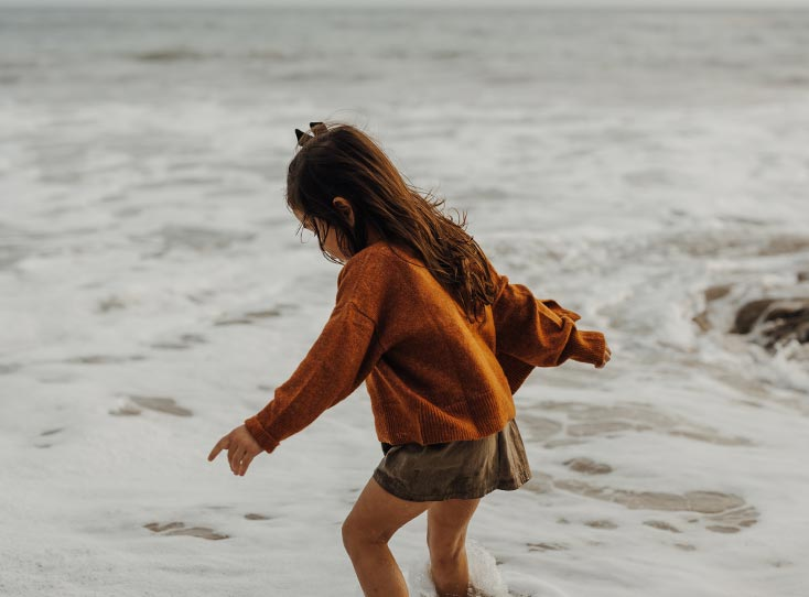 Little girl playing in coastal waters as the tide rolls in