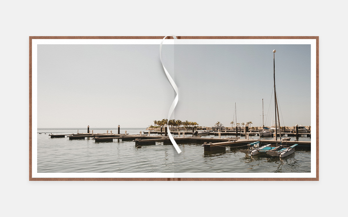 Two-age panoramic album spread of small sailboats at a dock