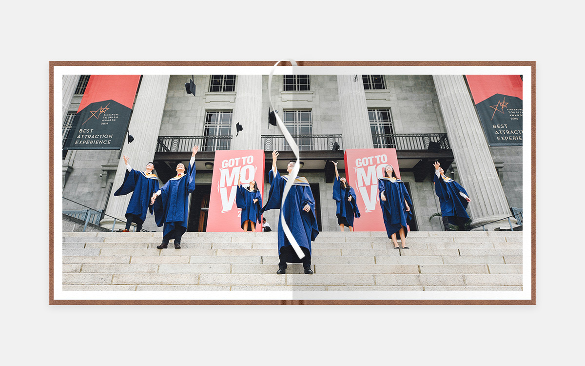 Two-page panoramic image of graduates throwing caps in the air