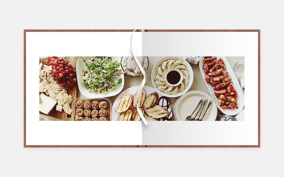Two-page panoramic album spread of table filled with delicious foods