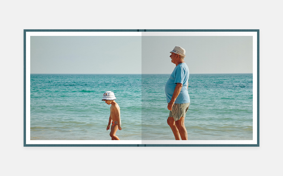 Two-page panoramic image in album of grandpa and little boy wearing matching hats and walking the beach