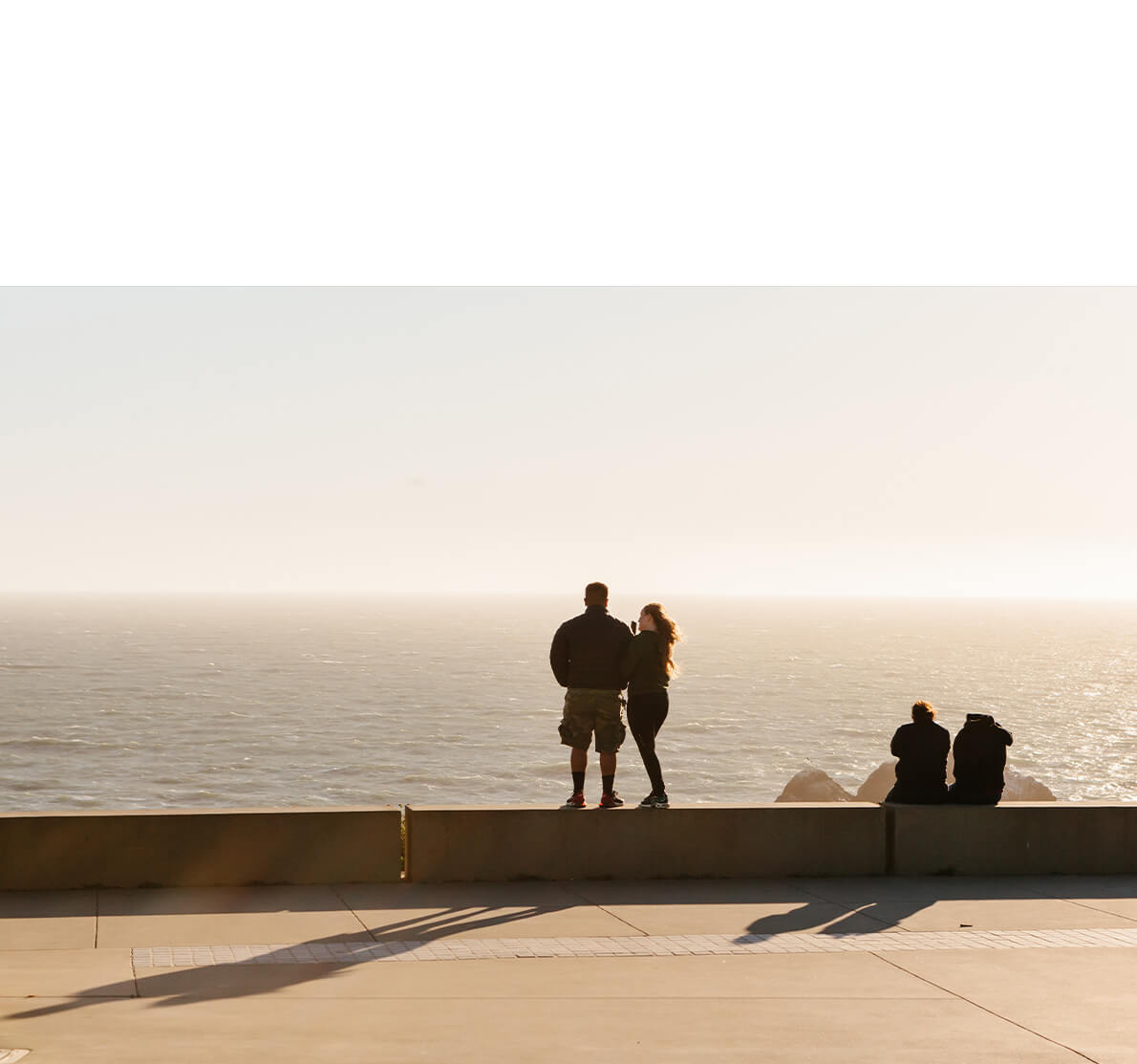 Photo by Brandon Lopez of couple standing on ledge by ocean