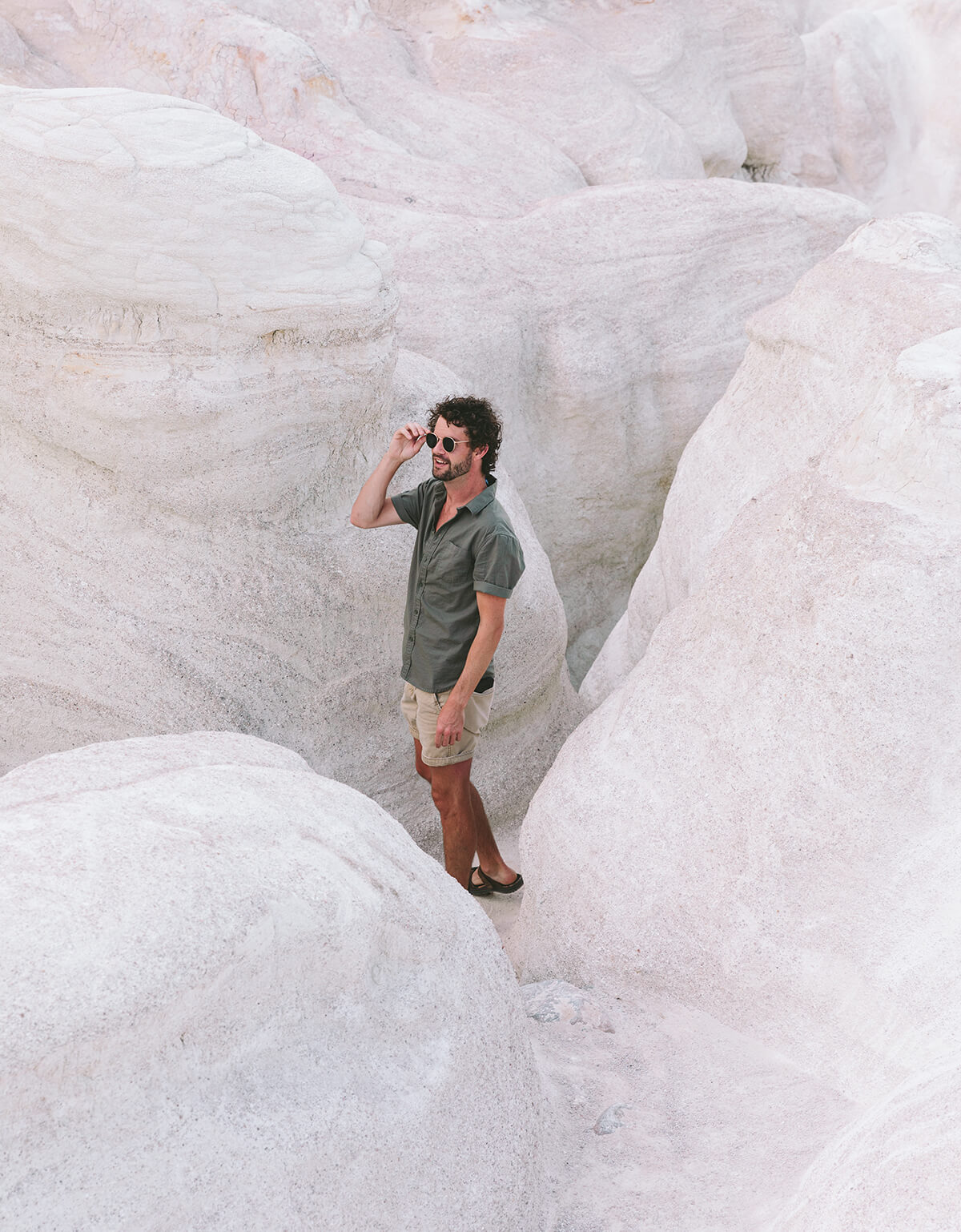 Photo of man standing inside of rock structure by Brandon Lopez