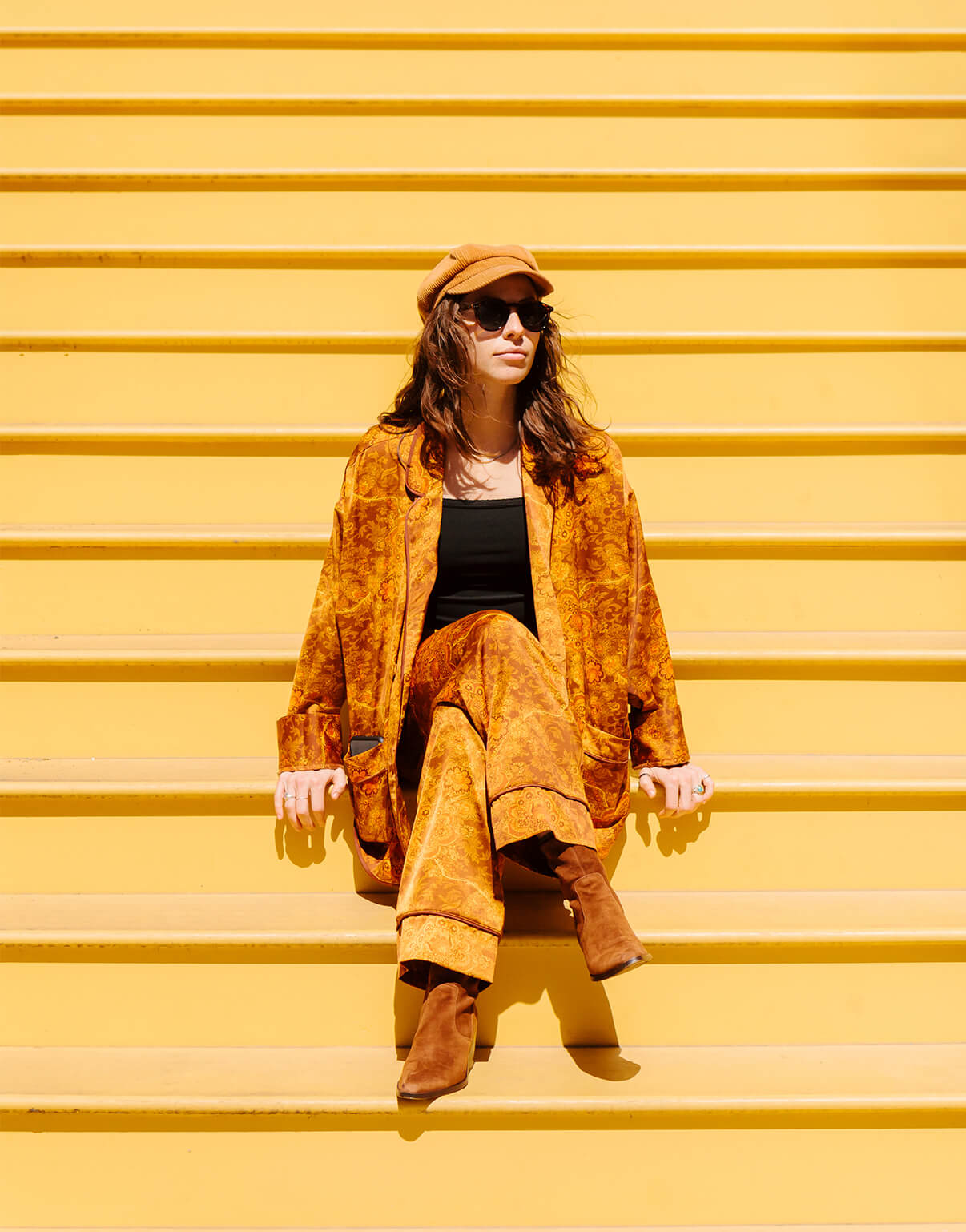 Photo by Brandon Lopez of velvet-clad woman sitting on endless yellow stairs