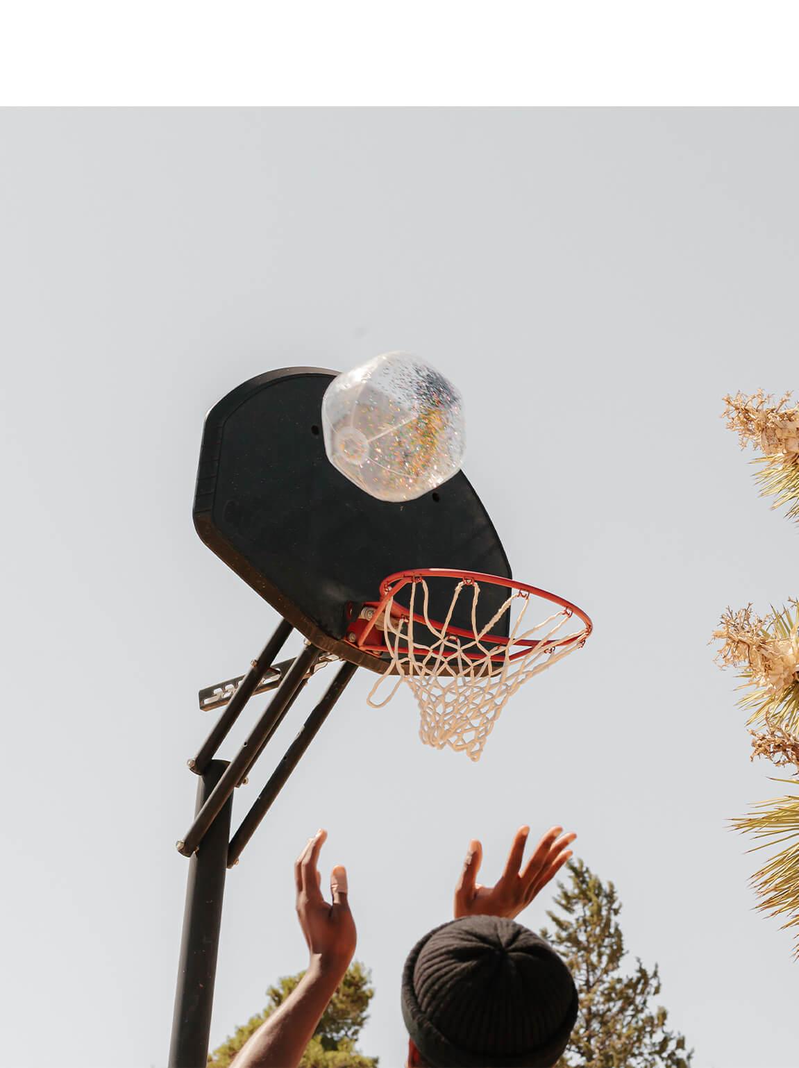 Photo by Brandon Lopez of hands shooting glittery beach ball into basketball hoop